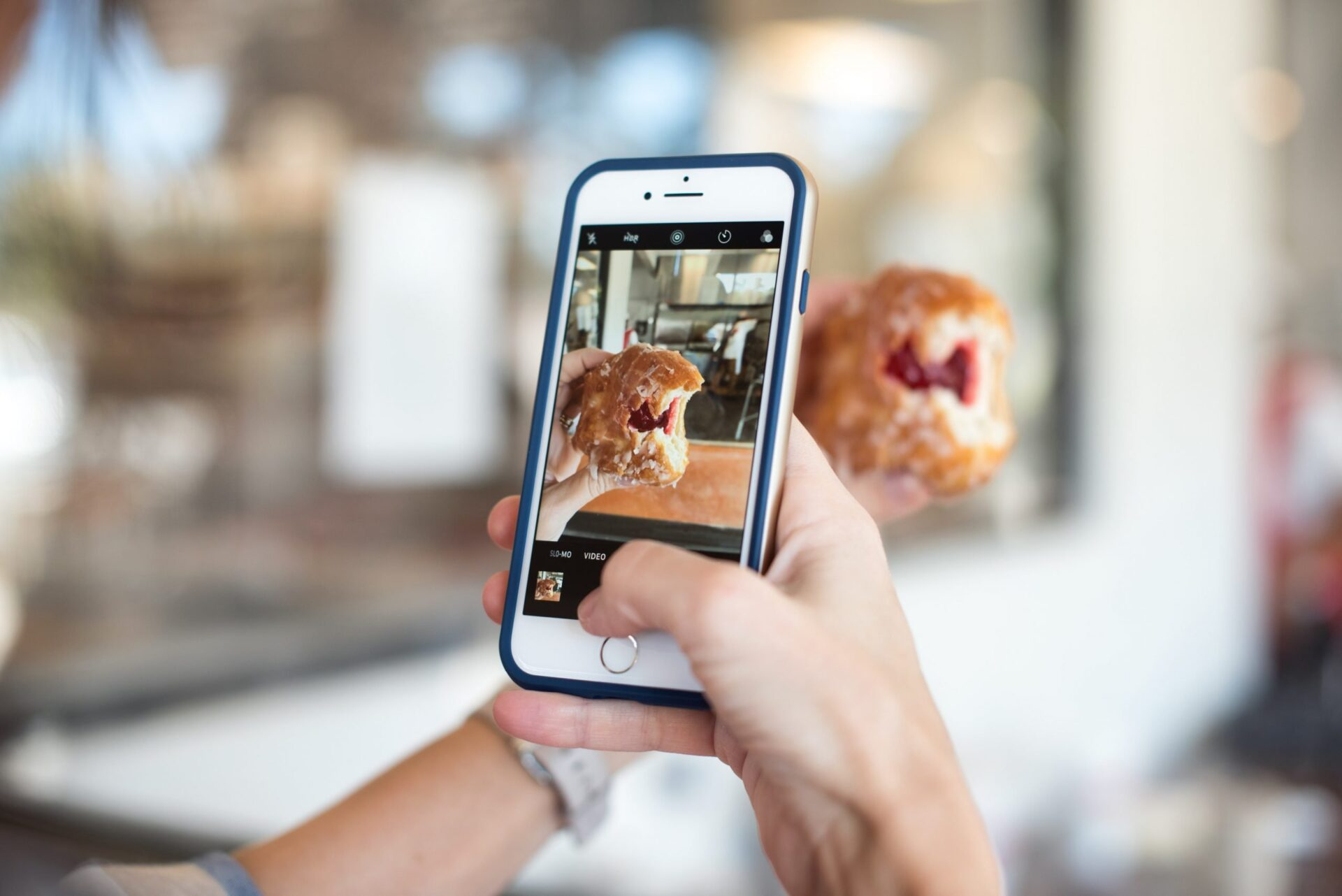 Mobile phone taking a photo of a donut